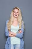 Young blond woman smiling with arms crossed Royalty Free Stock Photos