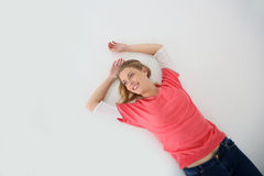 Young blond woman smiling lying on the floor Royalty Free Stock Image