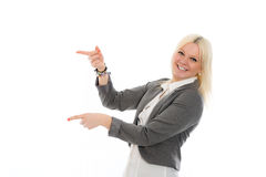 Young blond woman is smiling and pointing sideward Stock Image