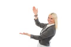 Young blond woman is smiling and pointing sideward Royalty Free Stock Images