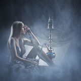 A young blond woman smoking a hookah on a foggy background Stock Photography
