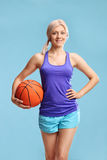 Young blond woman in sportswear holding a basketball Royalty Free Stock Image