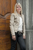 Young blond woman standing against a door Stock Photo