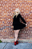Young Blond Woman Standing Against Red Brick Wall Stock Photo