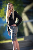 Young blond woman outdoors. Fashionable young woman with blond hair standing outdoors Stock Photography
