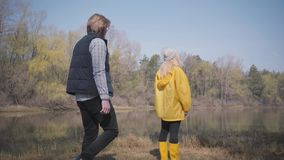Young blond woman standing looking at amazing view of river and forest and bearded handsome man come and hug girl. Rest. Young blond woman standing looking at stock video