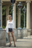 Young blond woman standing in the old Park among the stone columns. Stock Photos