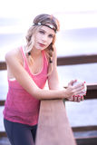 A young blond woman standing on a pier with a cup of coffee and her workout outfit. Stock Photography