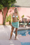 Young blond woman standing by pool Stock Images
