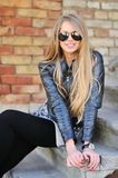 Young blond woman in a sunglasses. Stunningly beautiful young blond woman in a jacket and aviator sunglasses sitting on the stairs royalty free stock images