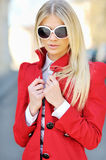 Young blond woman in sunglasses backli. Beautiful young blond woman in a red dress and sunglasses backlit stock image