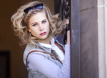 Young blond woman with sunglasses on her head holding a rod iron door. Stock Photos