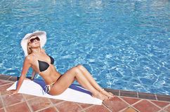 Young blond woman at swimming pool. Young blond caucasian white woman wearing black bikini, hat and sunglasses. Model sitting at swimming pool. 3/4 view Royalty Free Stock Photography