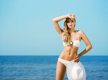 Young blond woman in a swimsuit posing on the beach Stock Images
