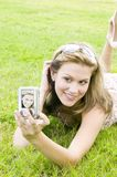 Young blond woman takes a self portrait with a camera. Very attractive young blond girl takes a self portrait of herself in  a sexy summer dress Stock Photo