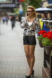 Young blond woman talking on the cell phone on the street Stock Image