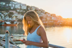Young blond woman texting message at sunset, Alanya, Turkey Royalty Free Stock Photography