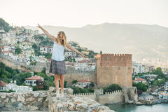 Young blond woman tourist balancing on ancient fortress wall of Alanya castle. Stock Photo