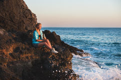 Young blond woman tourist sittig on rocks by the sea at sunset with bottle of lemonade. Alanya, Mediterranean region Stock Photo
