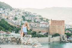 Young blond woman tourist sitting on ancient fortress wall of Alanya castle. Stock Images