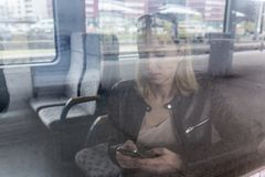 Young woman traveling by train, using smart phone. Stock Photo