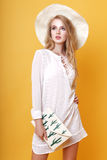 Young blond woman in tunic and hat in studio Stock Image