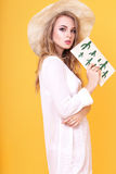 Young blond woman in tunic and hat in studio Stock Photography