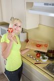 Young blond woman with vegetables on kitchen Stock Images