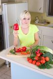 Young blond woman with vegetables on kitchen Stock Image