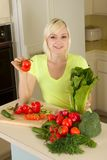 Young blond woman with vegetables on kitchen. Caucasian female presenting tomatoes and lettuce holding in hands by kitchen countertop Stock Photos