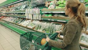 Young blond woman walk along shelves with greenery in supermarket stock video footage