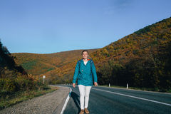 Young blond woman walking along an empty road. Royalty Free Stock Photo