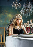 Young blond woman wearing crown in fairy luxury interior with em Royalty Free Stock Images