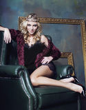 Young blond woman wearing crown in fairy luxury interior with empty antique frames total wealth long legs royalty free stock images