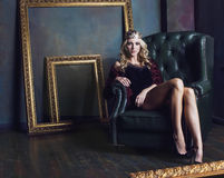 Young blond woman wearing crown in fairy luxury interior with empty antique frames total wealth long legs Royalty Free Stock Photography
