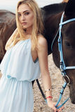 Young blond woman wears elegant dress, posing with black horse Royalty Free Stock Image