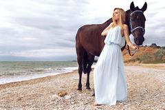 Young blond woman wears elegant dress, posing with black horse Stock Photos