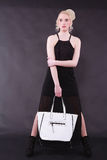 Young blond woman with white bag Stock Photos