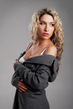 A young blond woman in a white bra and a grey coat Royalty Free Stock Photos