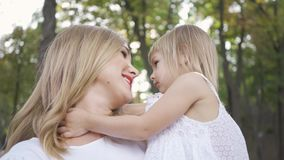 Young blond woman in white caressing her cute daughter. Daughter hugging her mother. Leisure outdoors. Happy family. One. Parent. Motherhood, parenthood, happy stock video footage