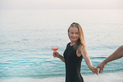 Free Young Blond Woman With Glass Of Rose Wine Holding Man S Hand On Beach By The Sea At Sunset. Alanya, Turkey. Stock Image - 75662991