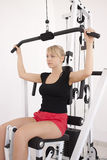 Young blond woman workout in gym. Young blond caucasian woman working out in gym. Pumping iron while sitting, lifting weight exercise. 3/4 view. Serious facial Stock Image