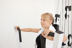 Young blond woman workout in gym. Young blond caucasian woman working out in gym. Pumping iron while sitting, lifting weight exercise. 3/4 view. Happy facial Stock Images
