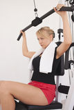 Young blond woman workout in gym. Young blond caucasian woman working out in gym. Pumping iron while sitting, lifting weight exercise. Side view. Serious facial Royalty Free Stock Photo