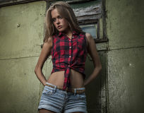 Young blonde woman. Posing and standing against a wall wearing  blue denim shorts and red check shirt Stock Image