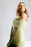 Young blond woman wrapped in light-yellow cloth Royalty Free Stock Images