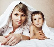 Young blond woman with little boy in bed, mother and son, happy familyyoung blond woman with little boy in bed, mother Stock Photos