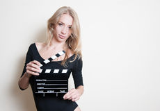 Young blonde actress starting audition. Young blonde woman actress in black shirt posing for audition with movie clapper board, looking at camera royalty free stock photos