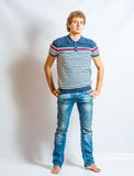 Young blonde adult caucasian man in casual clothes. Full Body Shot  Young blonde adult caucasian man in casual clothes on a gray background Stock Photography