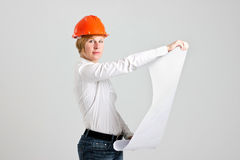 Young Blonde Architectures is Holding Architectural Plans. Young Architectures in Orange Safety Helmet is Looking to Architectural Plans  on White Background Stock Photography